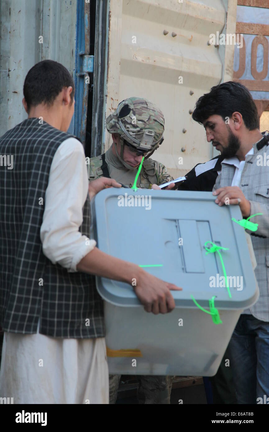 Afghan workers unload ballot boxes as a U.S. Army officer documents the boxes? seal numbers July 22, 2014, in Charikar, - Stock Image