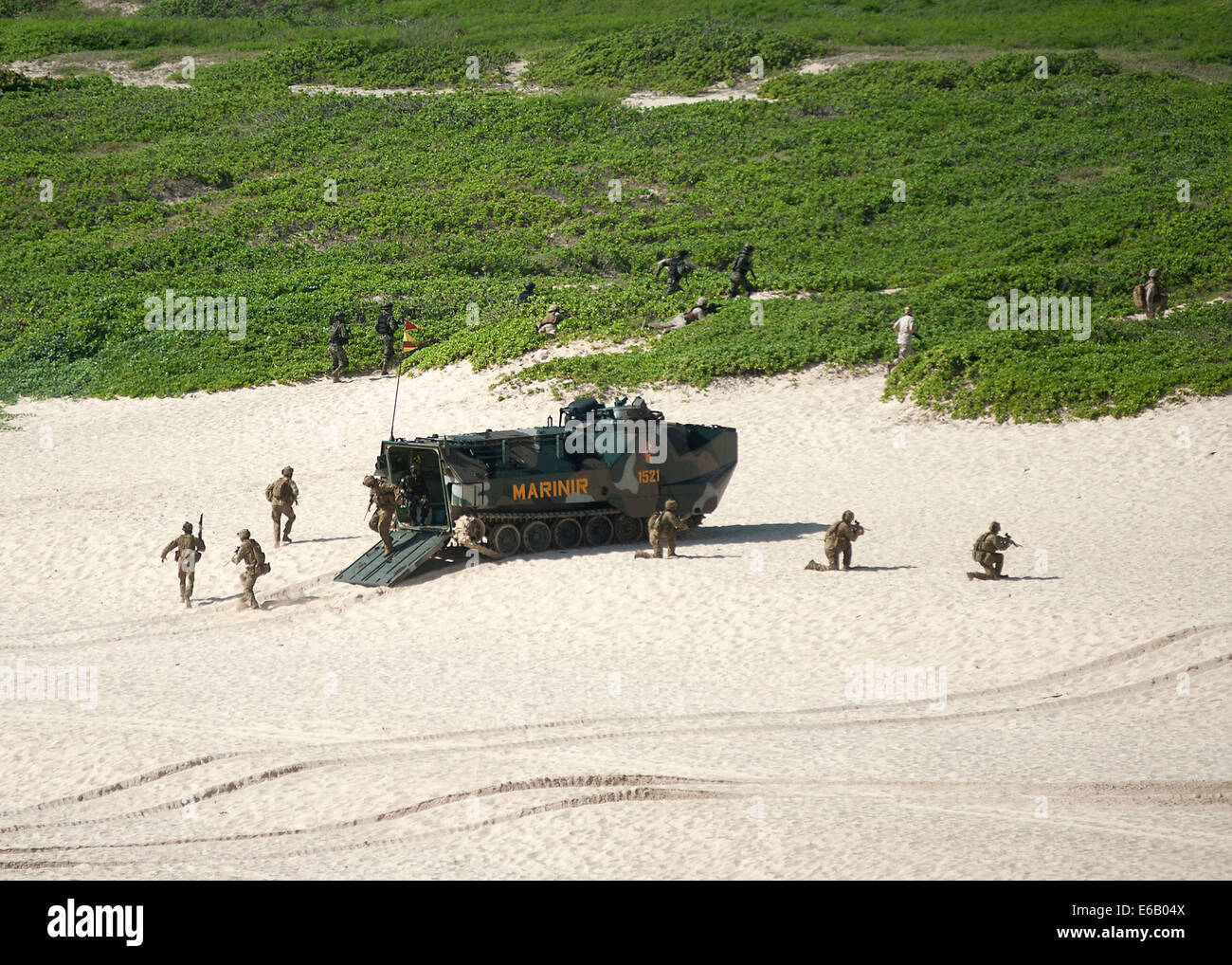 Foreign service members participate in an amphibious beach assault training exercise at Pyramid Rock Beach at Marine - Stock Image