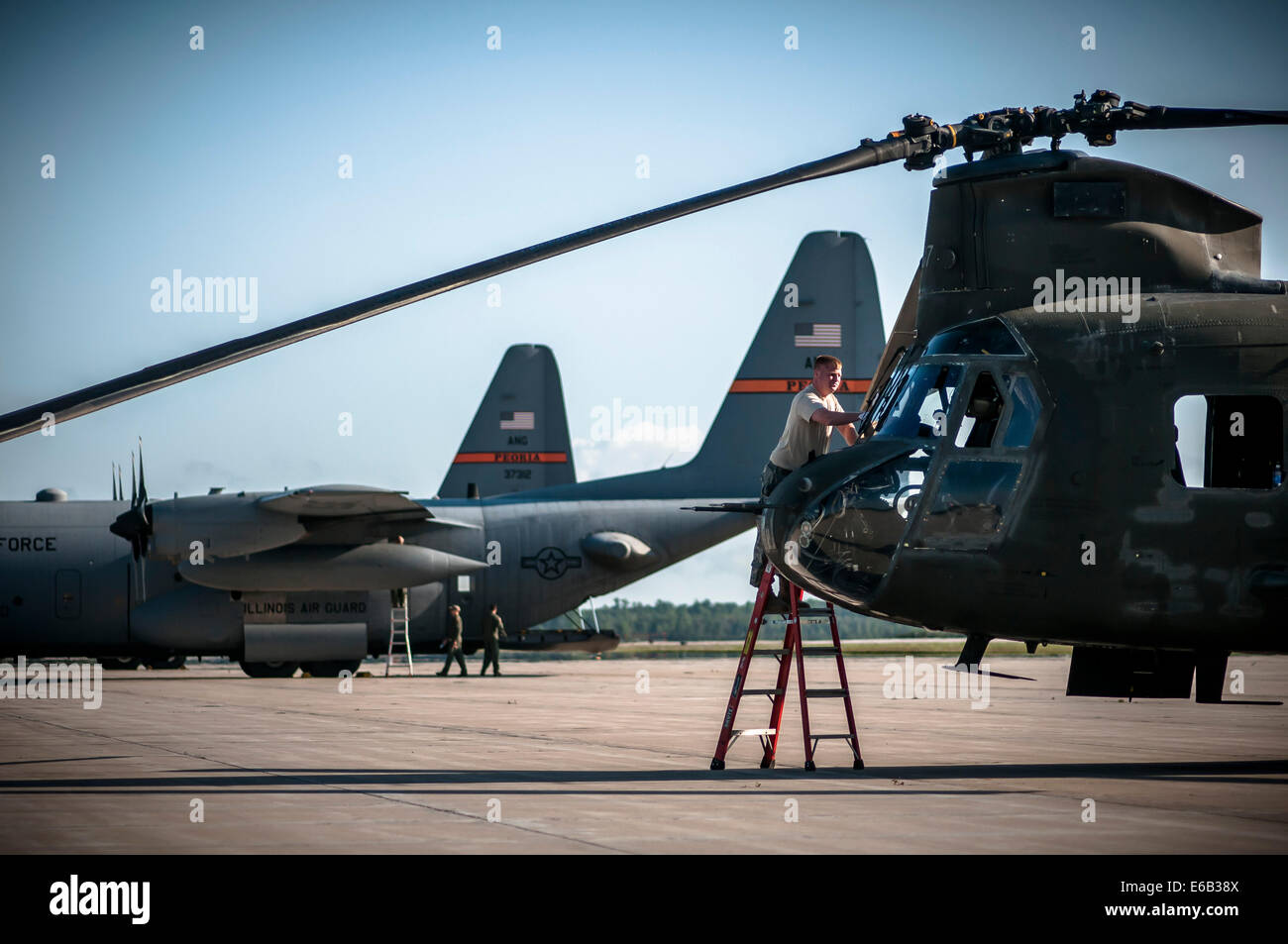 U.S. Army Staff Sgt. Justin Marshall washes cockpit windows during a preflight check on a CH-47 Chinook helicopter - Stock Image