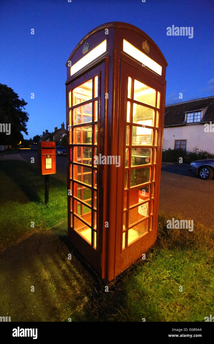 A traditional red telephone box at night in an English village, with a post box in the background. - Stock Image