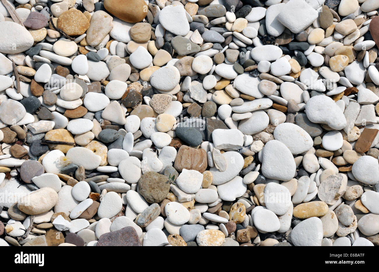 Closeup of smooth pebbles on beach. Makes an ideal background image for nautical themes. - Stock Image