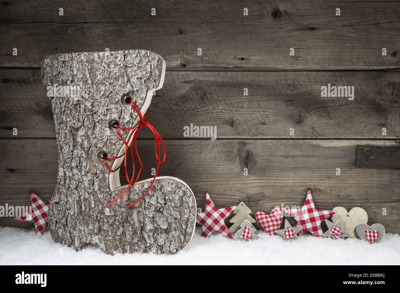 Xmas greeting card with santa boot in red and white colors on wooden background with snow. Idea for christmas decoration. - Stock Image