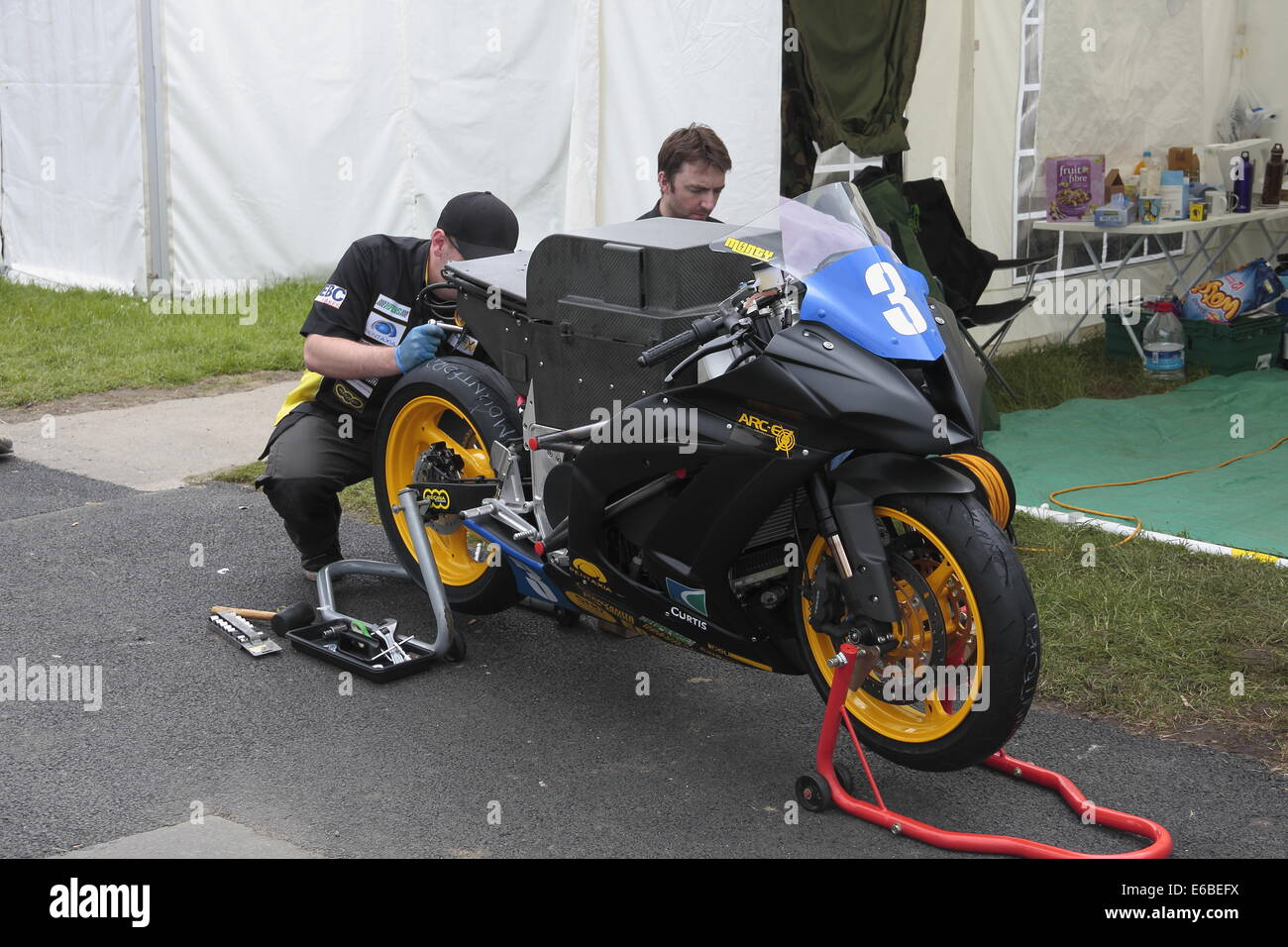 Brenden Rice and Matt Bagshawe working on the ARC-EV3 electric motorcycle, in the paddock for the 2014 Manx TT. Stock Photo