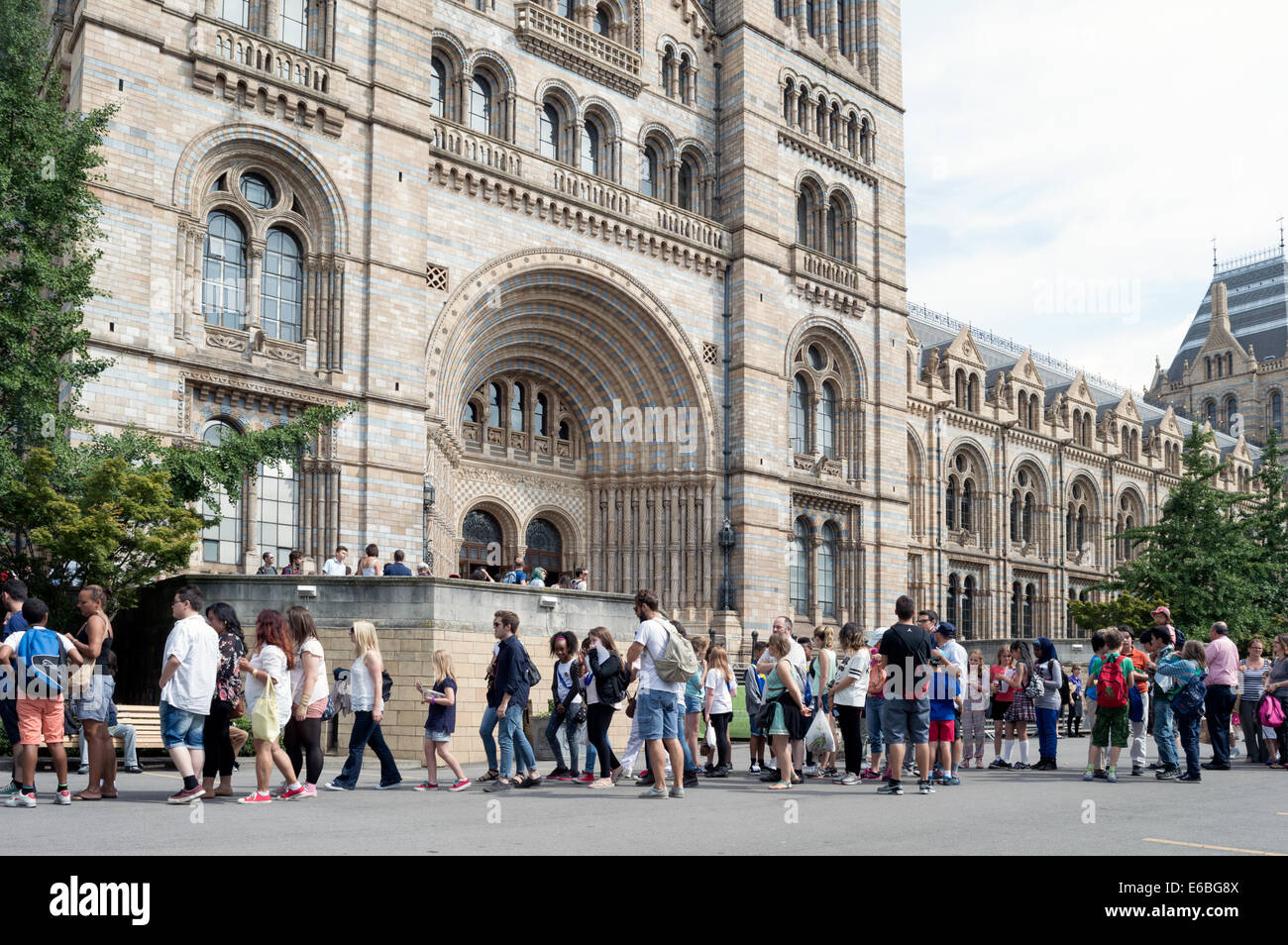 Visitors queuing outside the main entrance to the Natural History Museum London - Stock Image