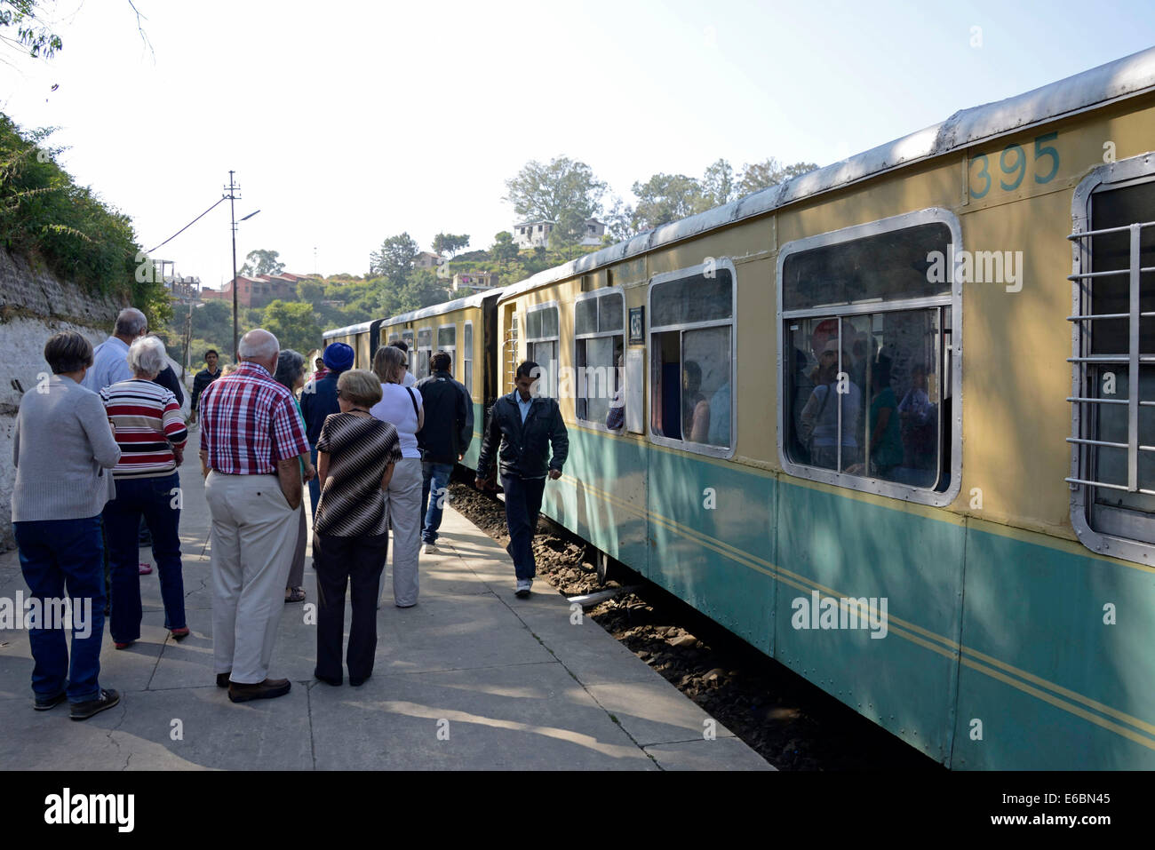 Tourists taking a break on the platform at Barog railway station whilst travelling on the Himalayan Queen train - Stock Image