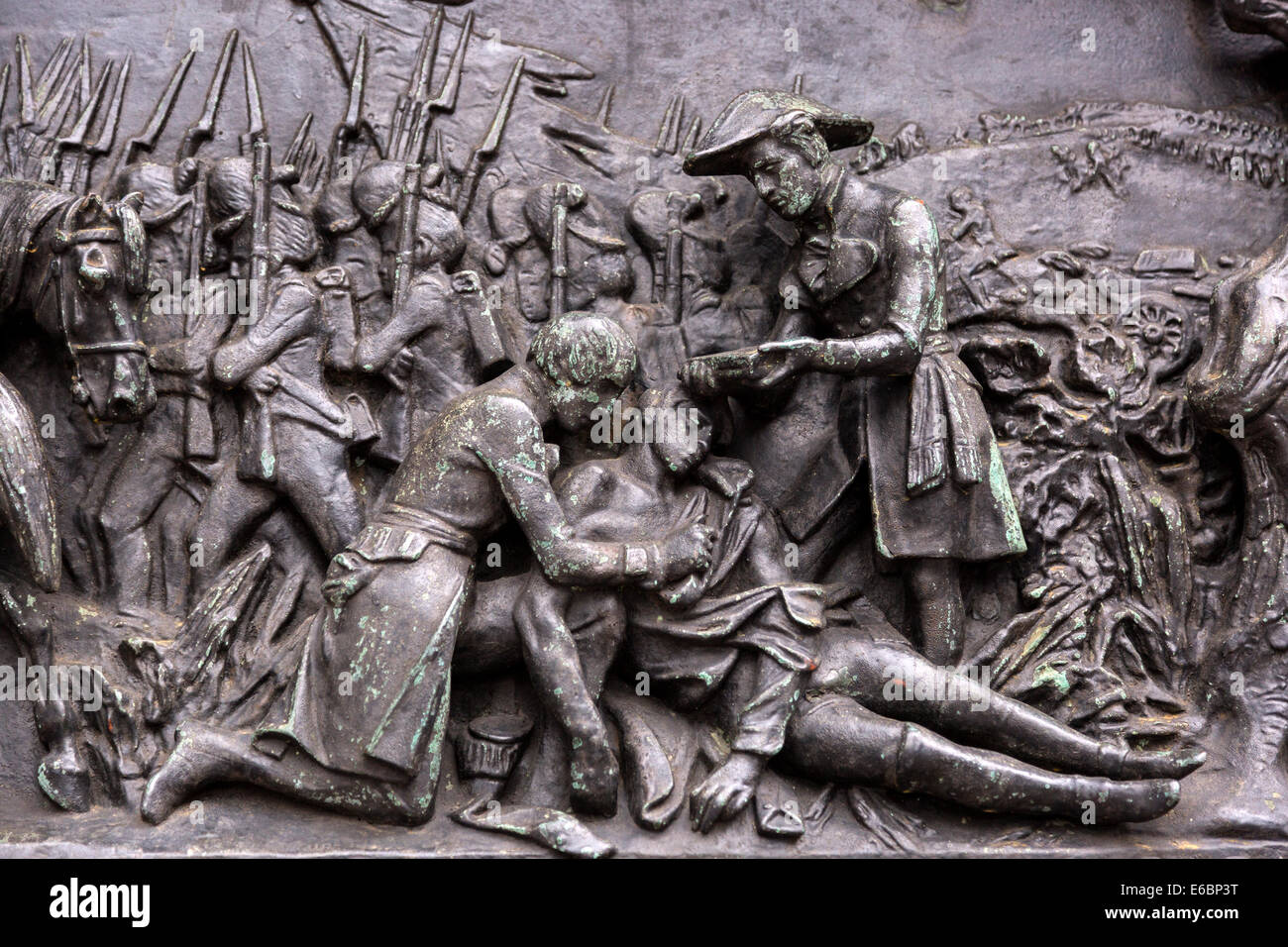 A war relief on the plinth of the Duke of Wellington statue, Glasgow, Scotland and the metal relief of a wounded - Stock Image