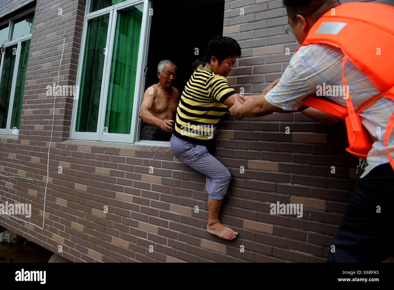 Lishui, China's Zhejiang Province. 20th Aug, 2014. A woman is evacuated as rain-triggered flood hit Lishui City, - Stock Image