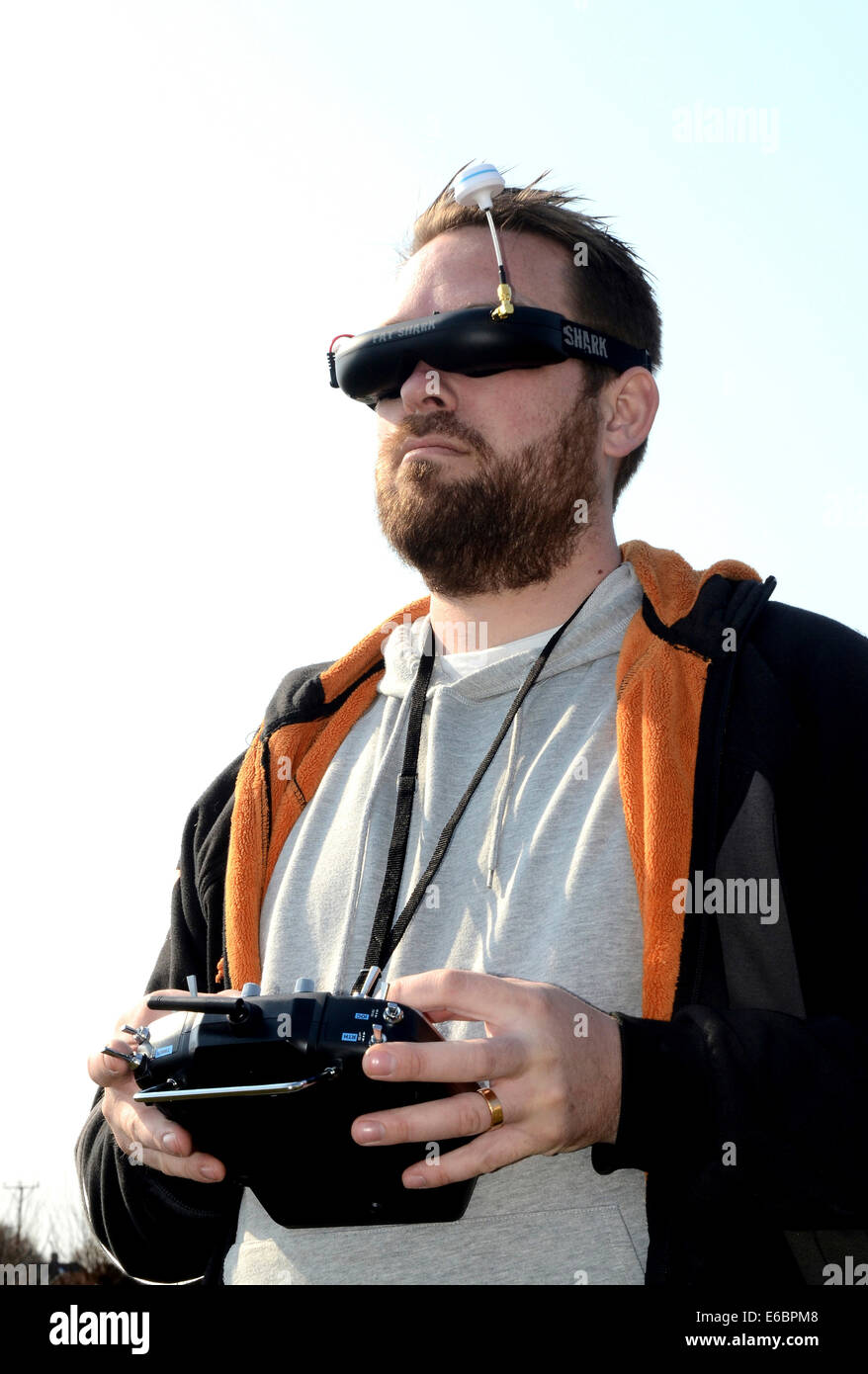 Man with FPV goggles and FUTUBA operator console to control a drone - Stock Image