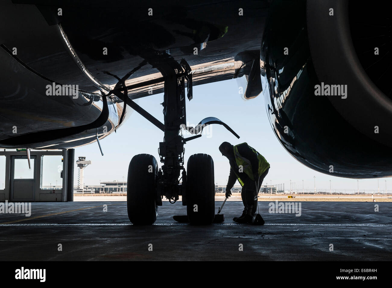 Man working on the undercarriage of an aircraft, Airport Berlin Brandenburg International, BBI, Berlin, Germany - Stock Image