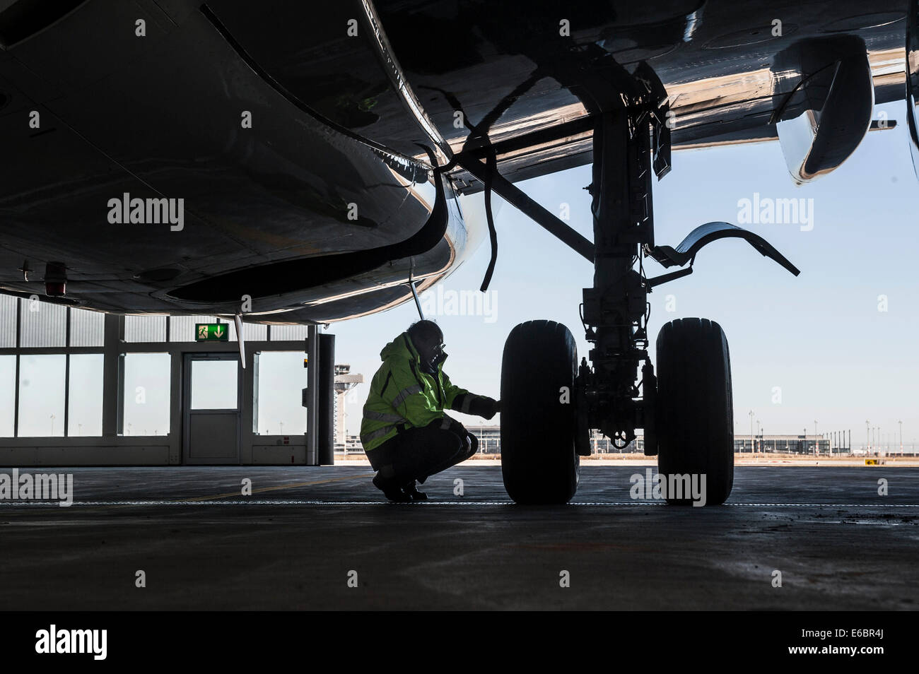 Worker kneeling next to at the undercarriage of an aircraft, Airport Berlin Brandenburg International, BBI, Berlin, - Stock Image