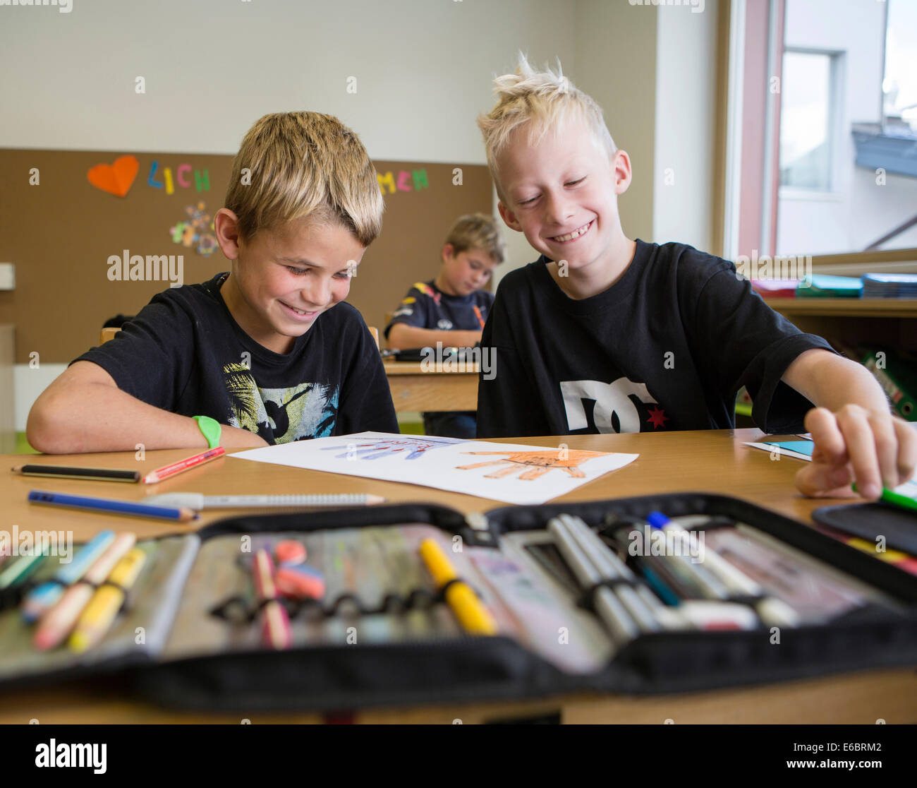Smiling children sitting in a primary school class during a drawing lesson, Reith im Alpbachtal, Kufstein district, - Stock Image