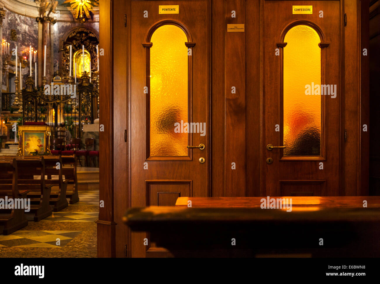 Priest hearing confession in confessional box booth in Roman Catholic Church Sanctuary of the Madonna di San Luca - Stock Image