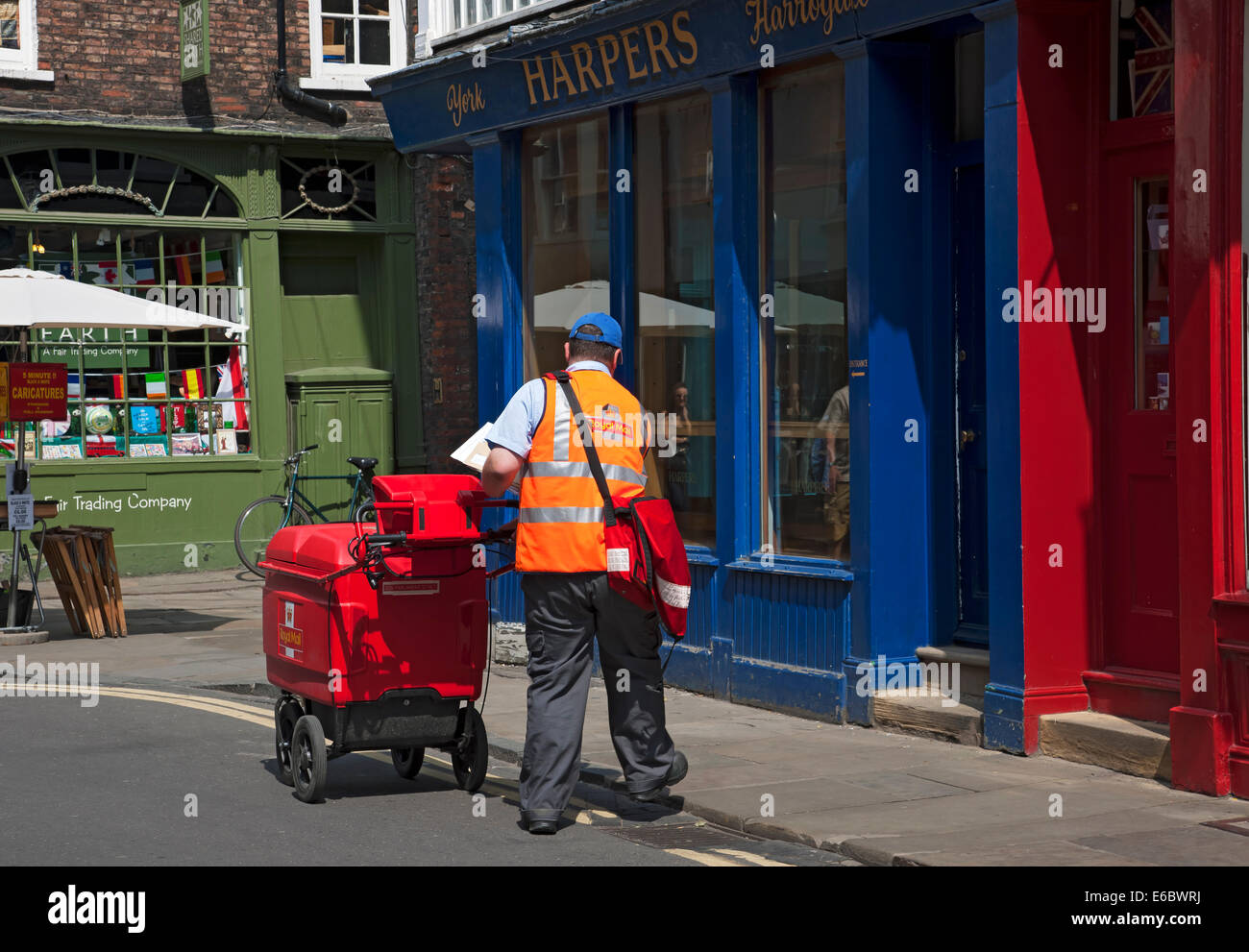 Postman pushing trolley delivering post letters mail in the city town centre York North Yorkshire England UK United Stock Photo