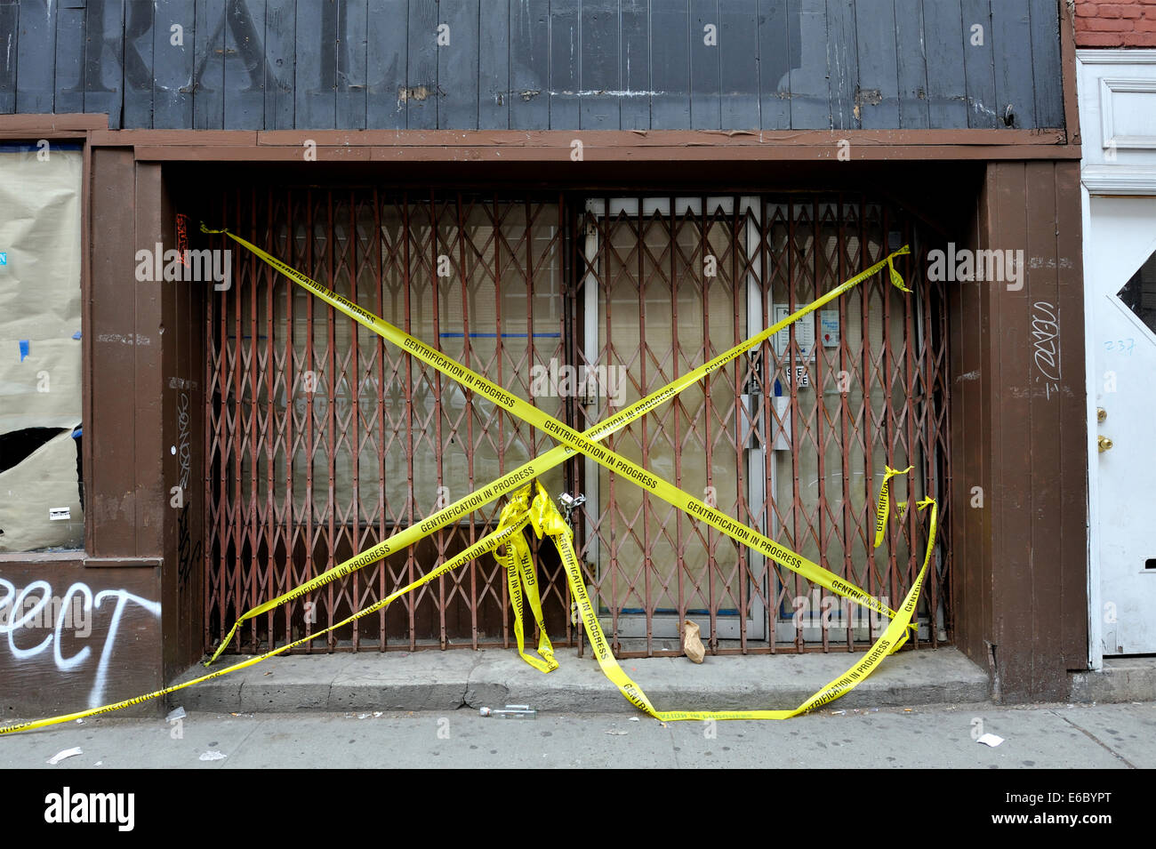Boarded up entrance to  building, with tape indicating 'Gentrification in Progress'. New York - Stock Image