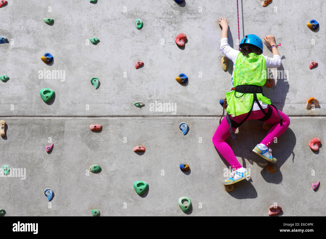 Youngster's effort in climbing a wall to reach the top - Stock Image
