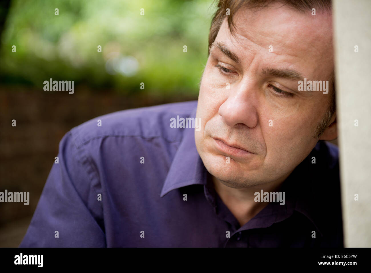 Portrait of a sad man, leaning his head against a wall. - Stock Image