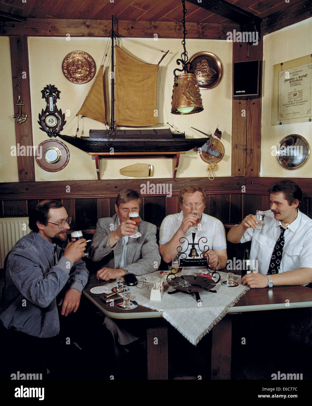 public house, group of regulars, four men sitting at a crackerbarrel drinking beer, quitting time, freetime, relaxation, - Stock Image