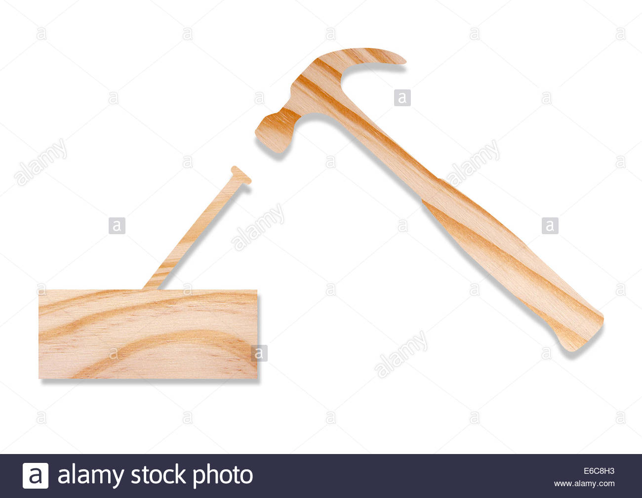 Hammer and nail shapes cut out of wood, isolated on white background ...