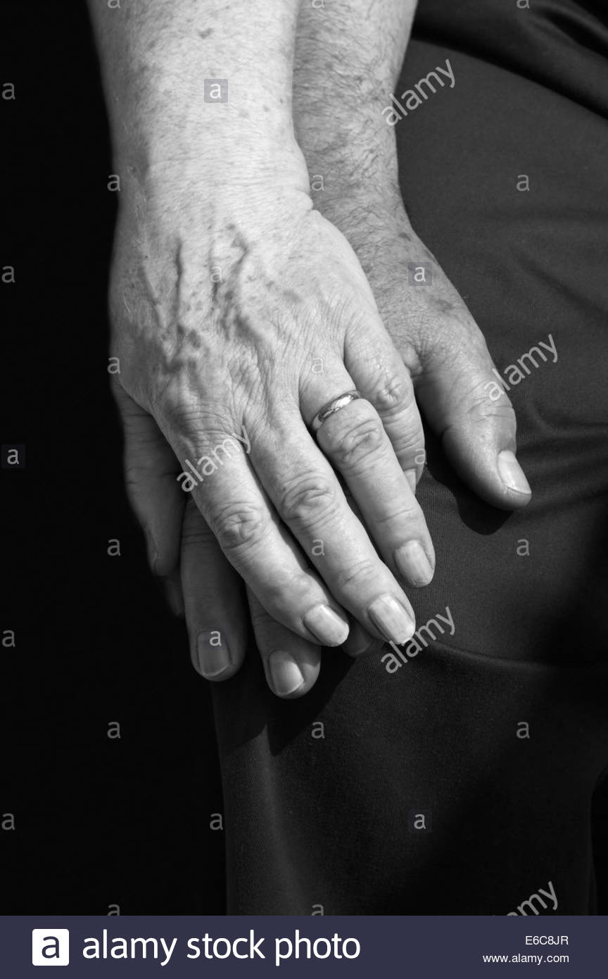 Close up of retired married couple sat together holding hands - Stock Image