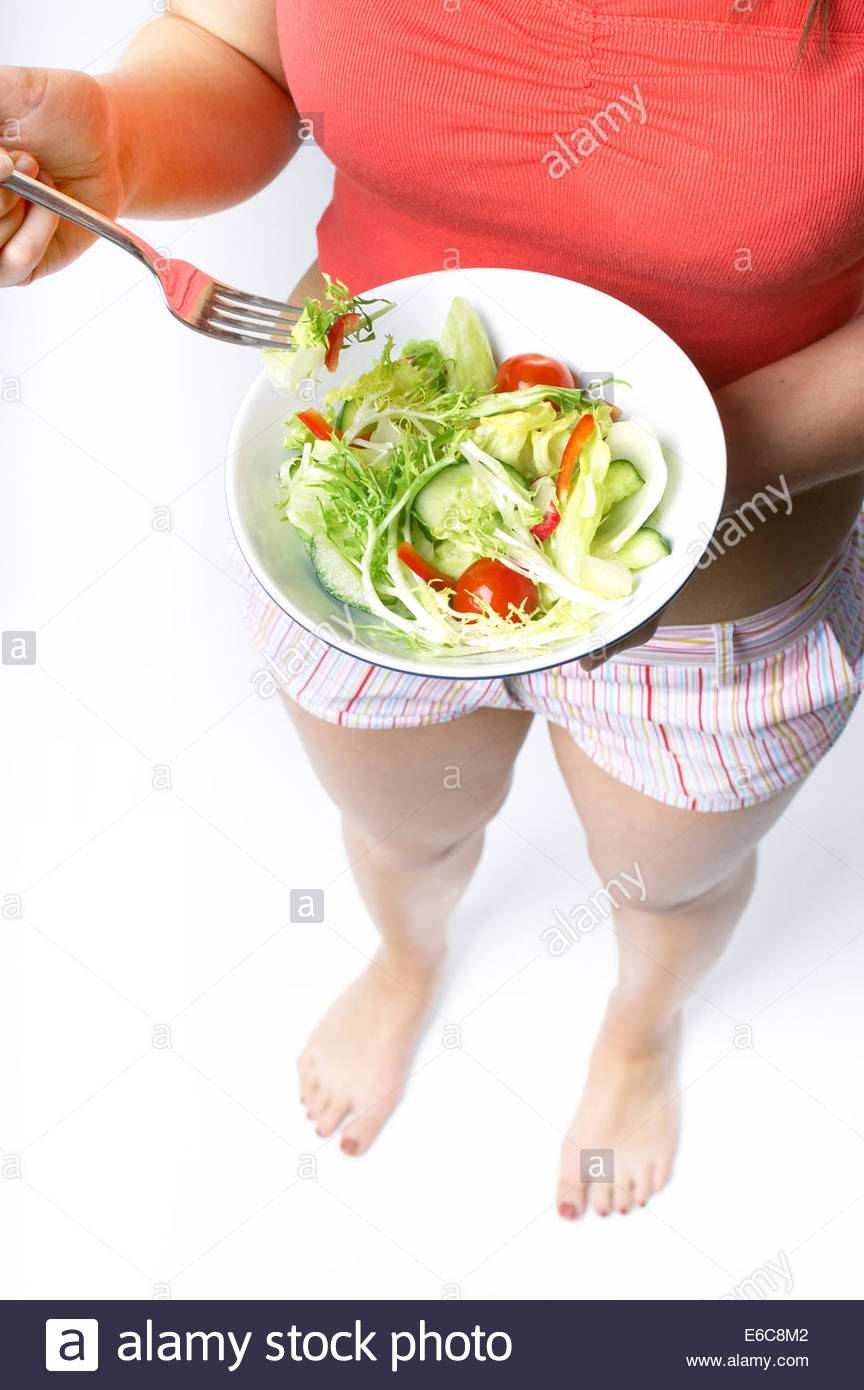 Young woman stood eating a bowl of healthy salad containing lettuce red peppers cucumber tomatoes and frisee - Stock Image