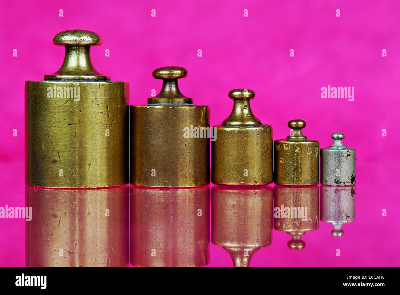 Five old-fashioned antique copper weights in a row - Stock Image