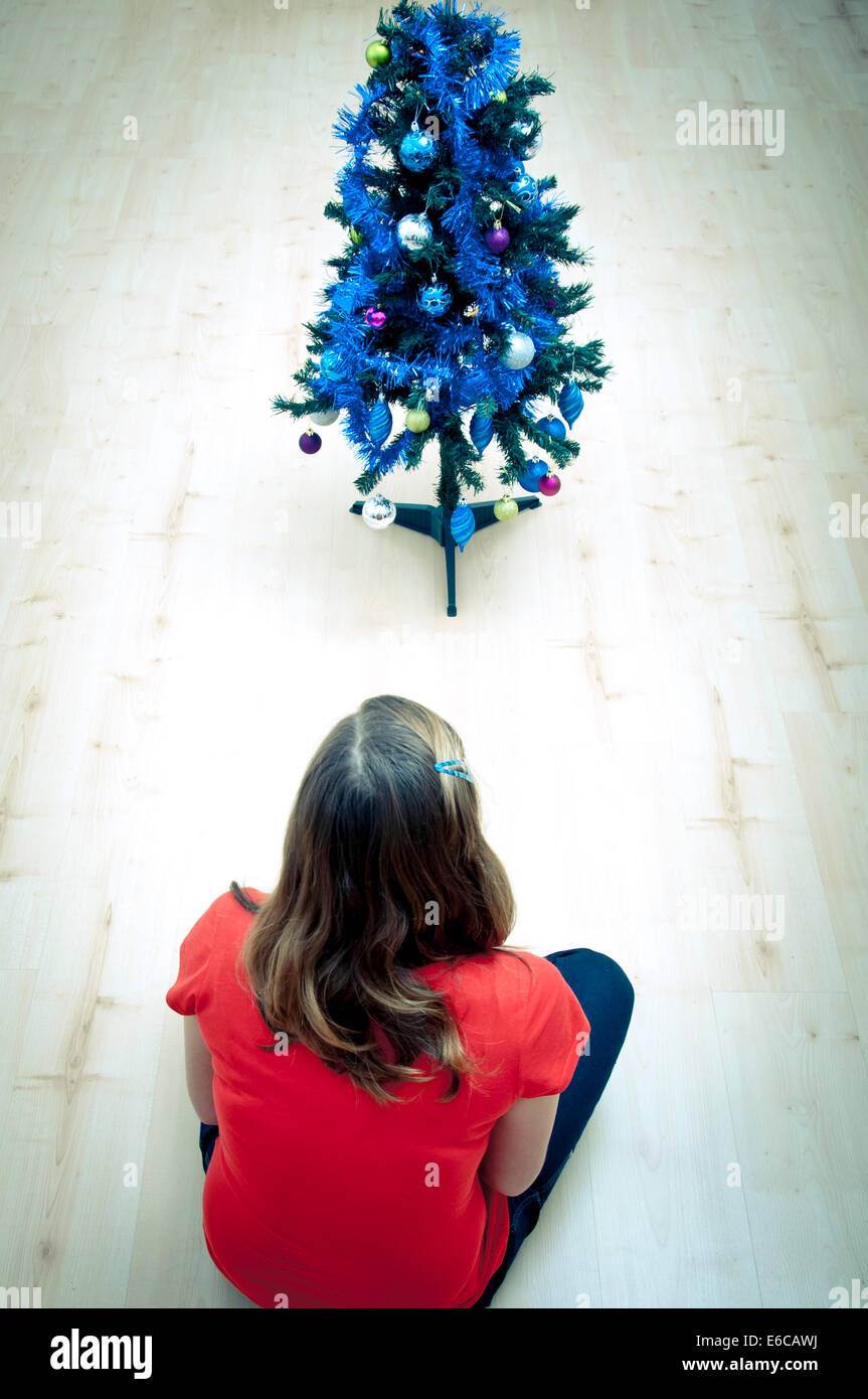 girl sitting in empty room in front of Christmas tree, no presents ...