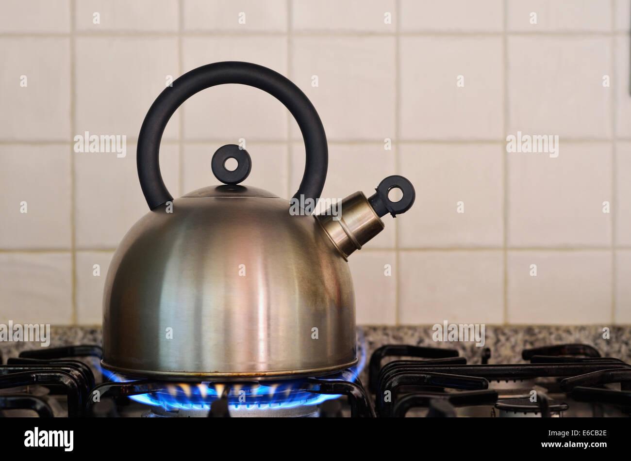 Teapot kettle on gas stove burner - Stock Image