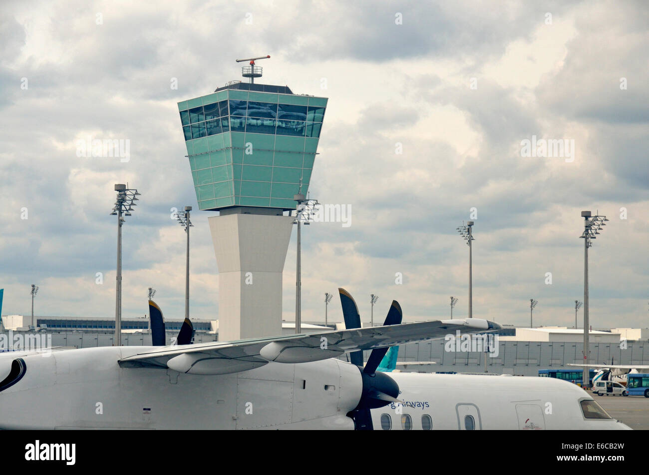 Stationary airplane on tarmac by Air Traffic Control Tower, Munich, Germany - Stock Image