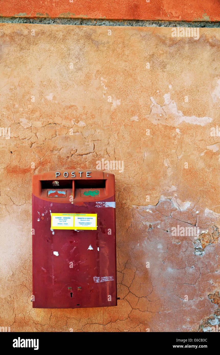 Red Italian mailbox on terracotta / ochre wall, Venice, Italy - Stock Image