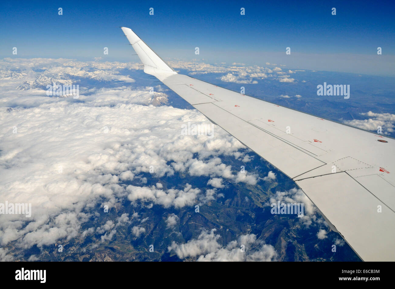 Wing of flying airplane over French Alps, France, Europe - Stock Image