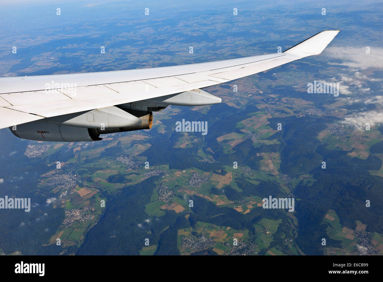 Wing of flying airplane over Germany, Europe - with tiny German villages below - Stock Image