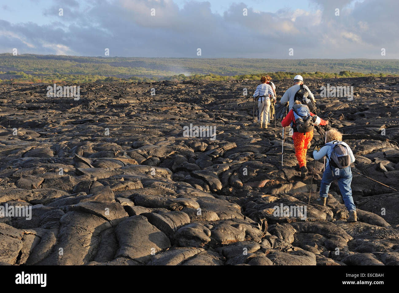 Group of hikers walking on cooled pahoehoe lava flow at sunrise, Kilauea Volcano, Big Island, Hawaii Volcanoes National - Stock Image