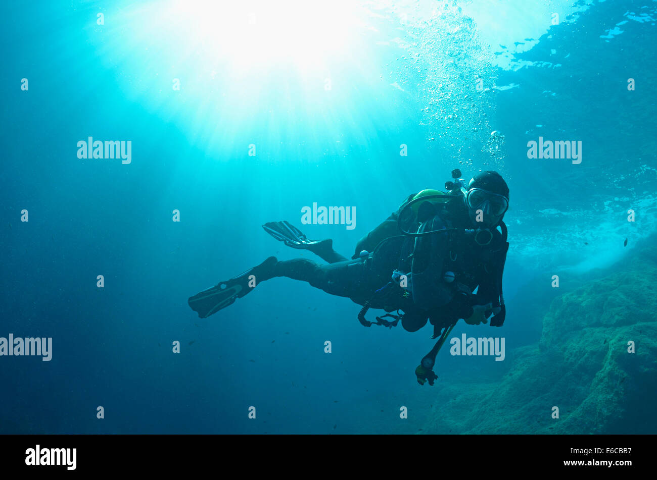 Sunbeams and scuba diver swimming underwater, Europe - Stock Image
