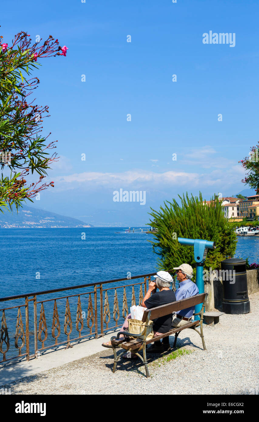 Elderly couple sitting eating lunch on the lakefront in Bellagio, Lake Como, Lombardy, Italy - Stock Image
