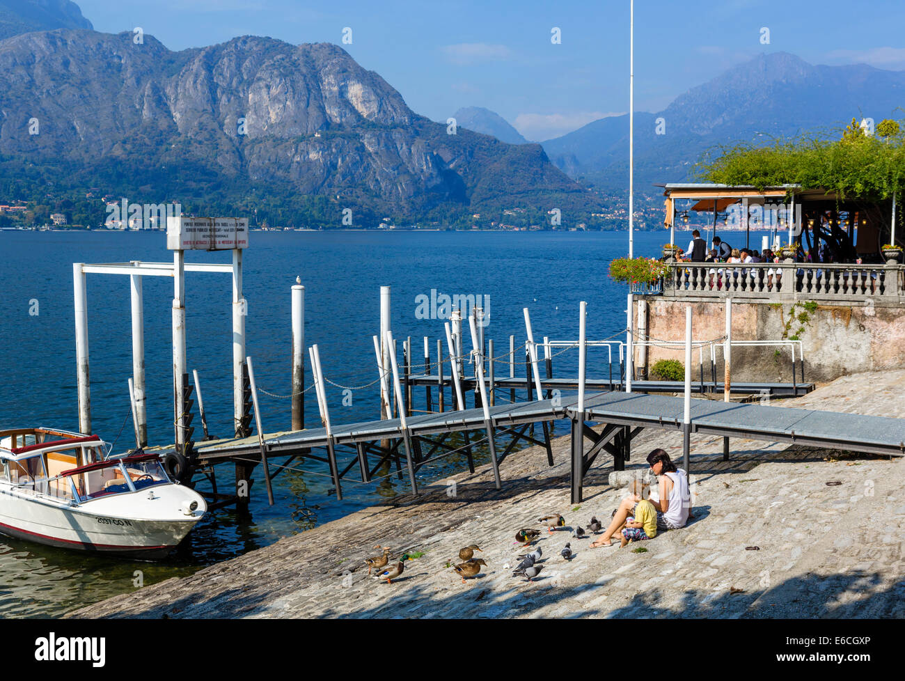 Mother and young son feeding ducks and pigeons on the lakefront in Bellagio, Lake Como, Lombardy, Italy - Stock Image