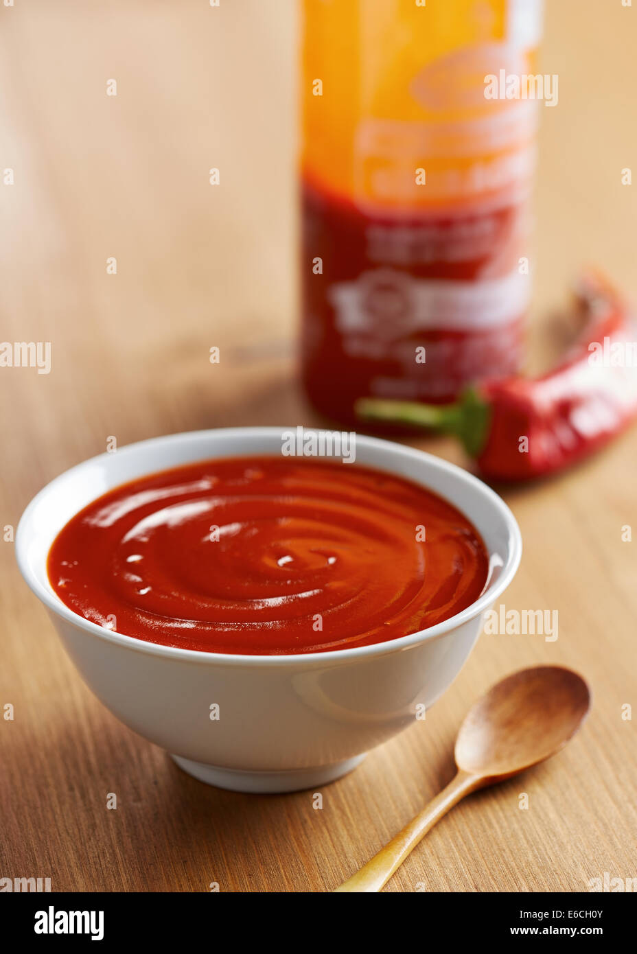 Bowl and bottle of sriracha sauce - Stock Image