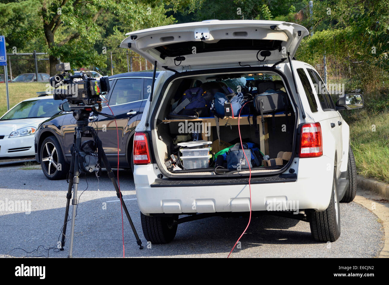 A TV cameraman's camera and his SUV loaded with camera supplies and equipment - Stock Image