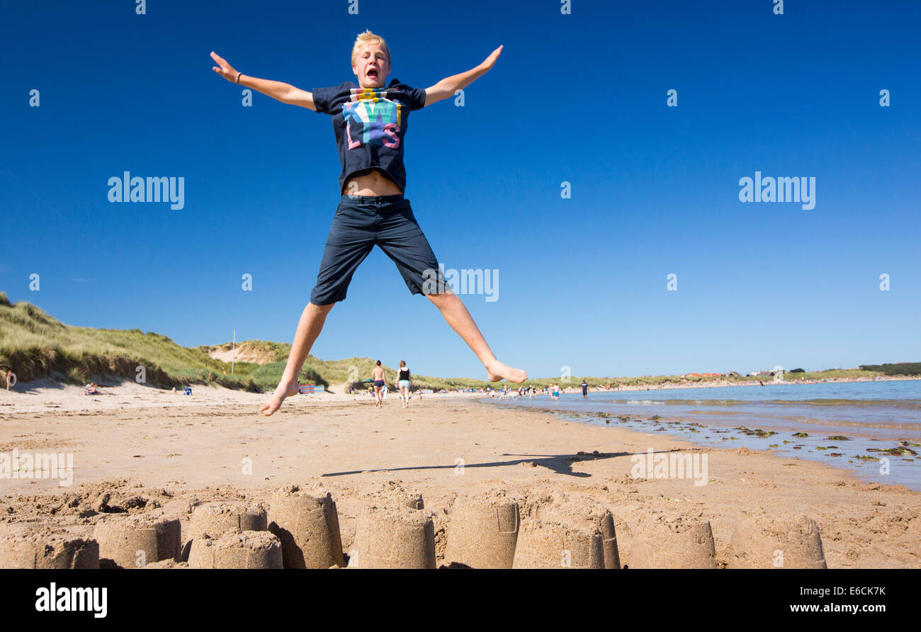 A boy jumping over a sandcastle on Bamburgh Beach, Northumberland, UK. - Stock Image