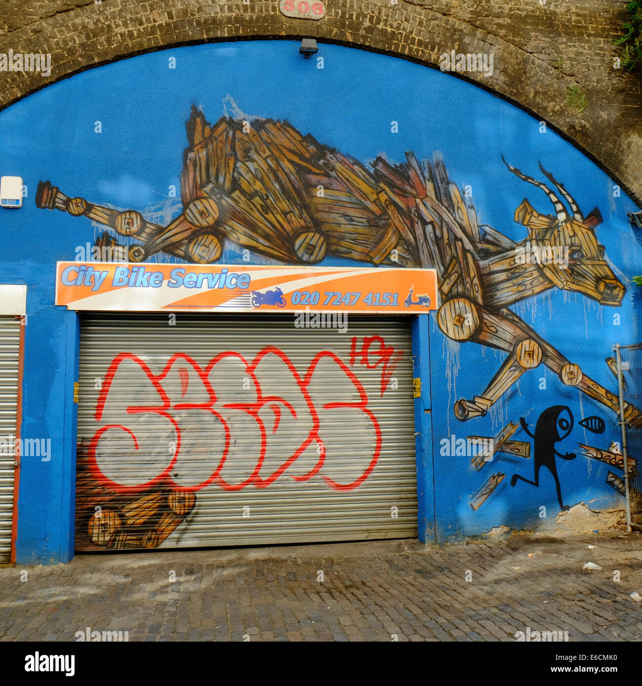 City Bike Service with leaping goats graffiti art in Shoreditch, London - Stock Image