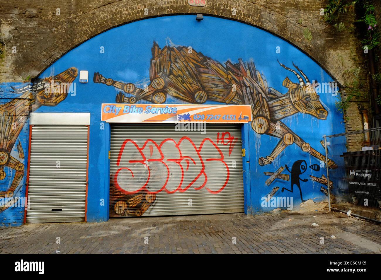 City Bike Service with leaping goats graffiti art in Shoreditch, London - Stock Image