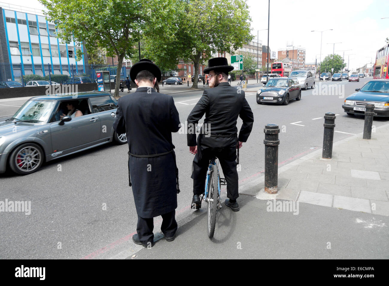 Orthodox Hasidic Jewish men with bicycle waiting to cross the road through traffic in Stamford Hill London N16  - Stock Image