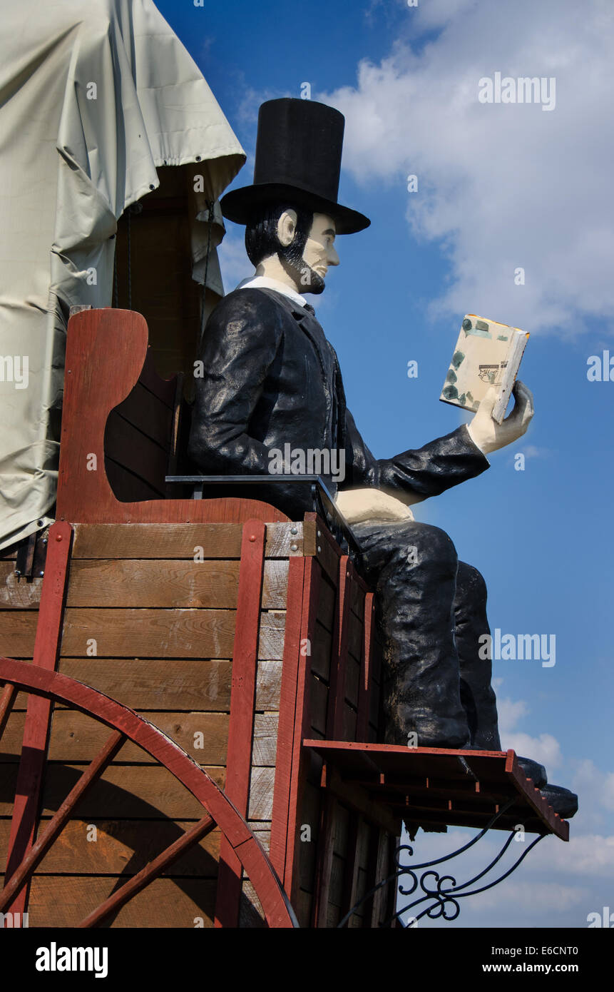 The Railsplitter Covered Wagon features Abraham Lincoln sitting on a covered wagon reading a book. - Stock Image