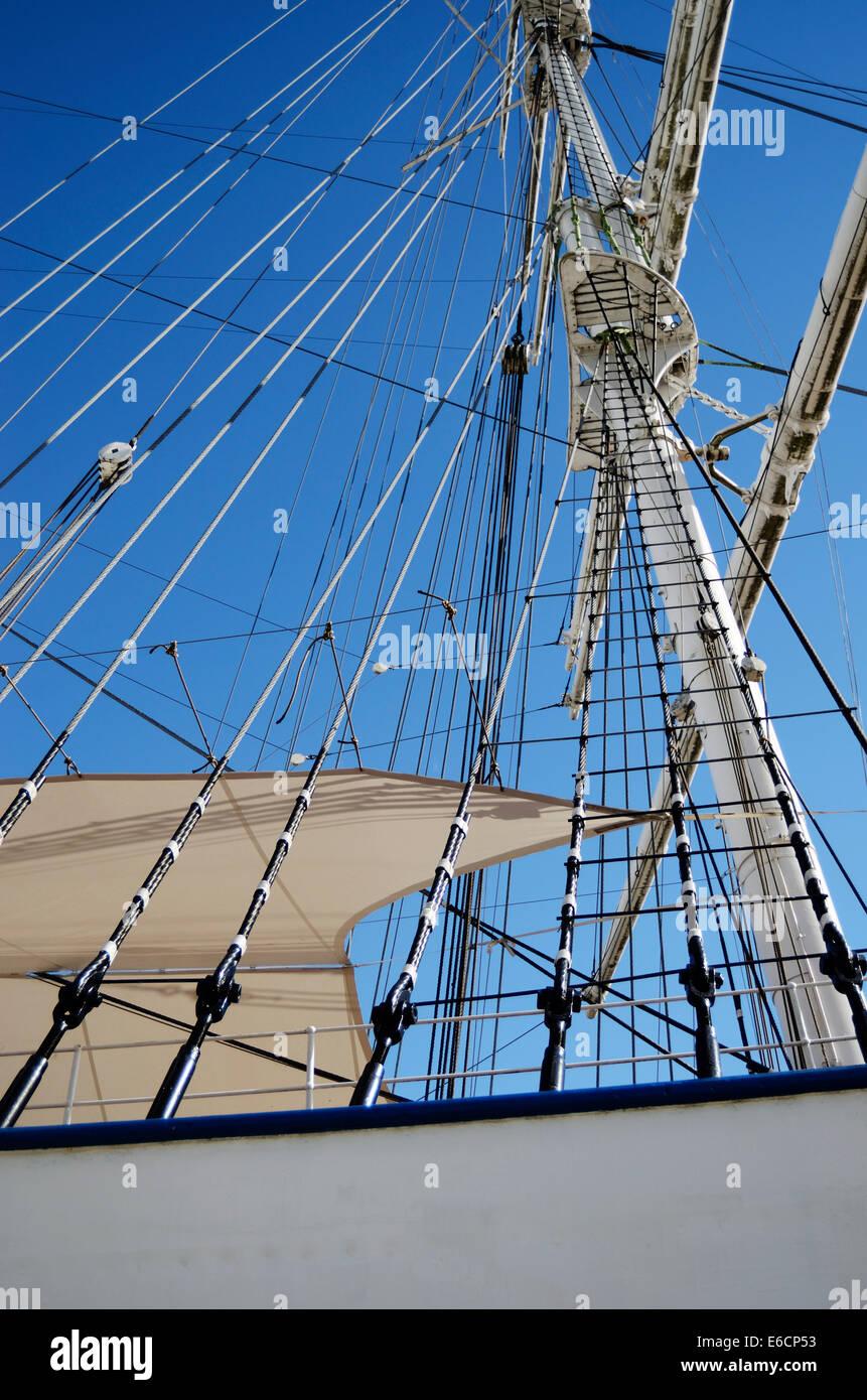 white sailboat mast on blue sky background - Stock Image