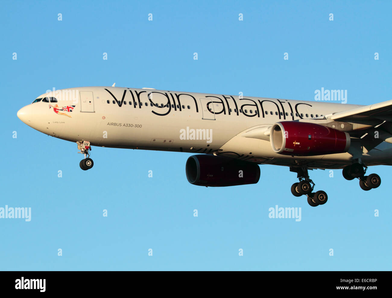 Virgin Atlantic Airways Airbus A330-300 long haul aircraft on final approach at sunset. Close-up of front section - Stock Image
