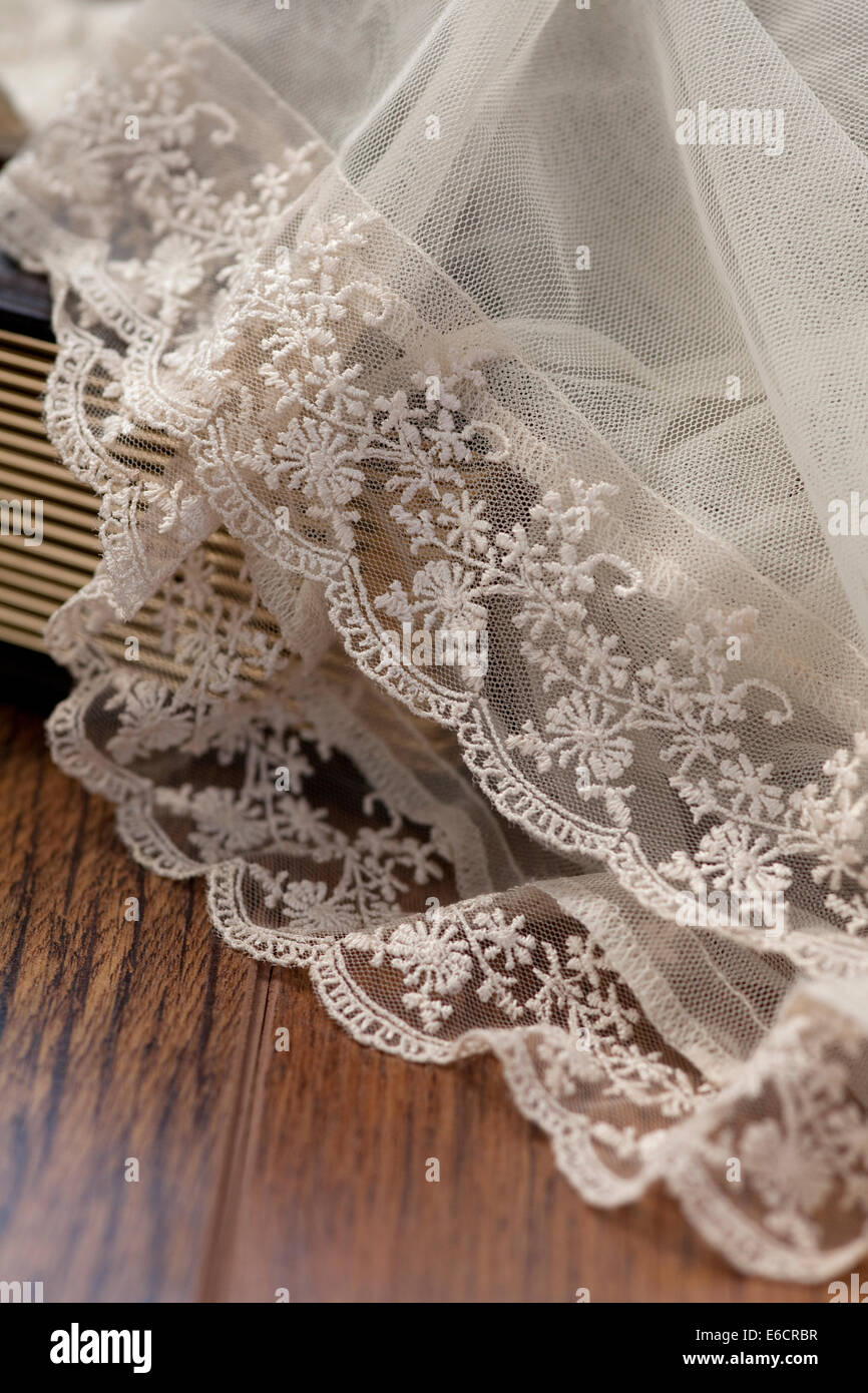 White lace bridal veil draped over a wooden floor and pages of a book. - Stock Image