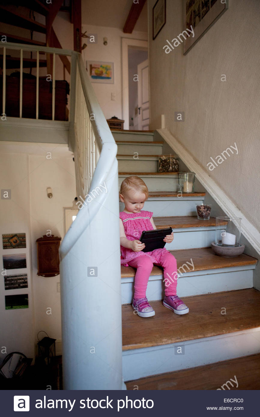 Toddler sitting on a flight of stairs in a house playing on a portable device. - Stock Image