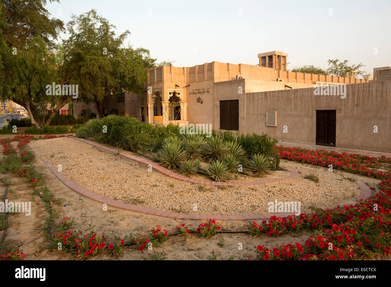 Garden with vivid red flowers, succulents and shading tree and exterior of Arabic restaurant in historic old sector - Stock Image