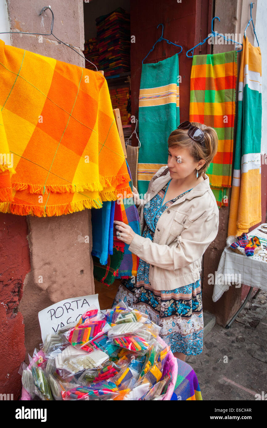A woman looks through the vividly colored tablecloths in Patzcuaro, Michoacan, Mexico. - Stock Image