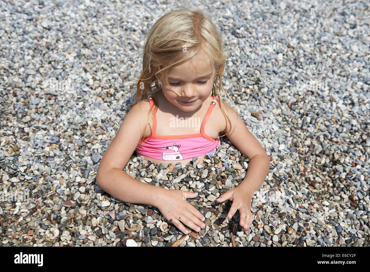 Child blond Girl buried in pebbles on beach, Lago di Garda, Lake, Torbole Nago, Italy - Stock Image