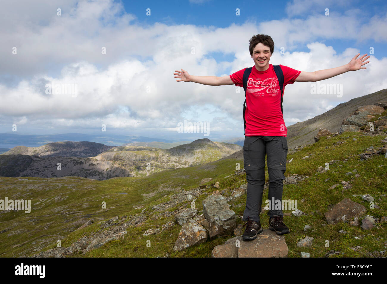 A teenage boy climbing Ben More, a Munro on the Isle of Mull, Scotland, UK. - Stock Image